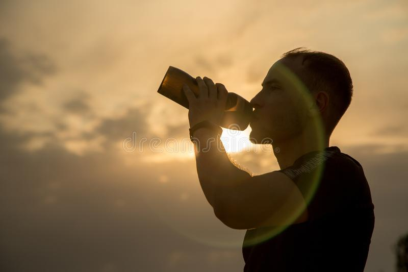 Portrait ,outline of a sporty young Caucasian guy in a black t-shirt and black shorts drinking water from a bottle at sunset.  royalty free stock images