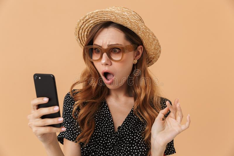 Portrait of outraged confused woman wearing straw hat and sunglasses holding and looking at mobile phone, isolated over beige royalty free stock photo