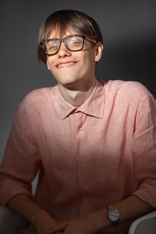Portrait of overjoyed funny young Caucasian man wearing glasses, shirt in a strip siting indoors with happy face and royalty free stock image