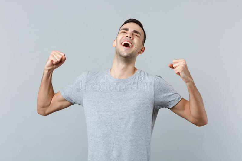 Portrait of overjoyed happy laughing young man in casual clothes clenching fists like winner isolated on grey wall royalty free stock image