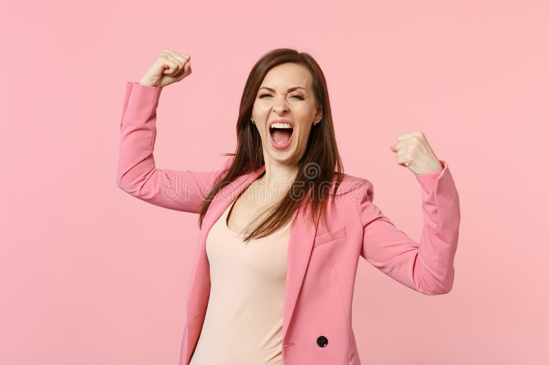 Portrait of overjoyed screaming young woman in jacket clenching fists like winner isolated on pastel pink wall stock photo