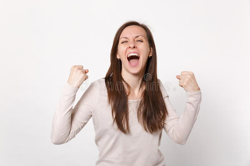 Portrait of overjoyed screaming young woman in light clothes keeping eyes closed doing winner gesture isolated on white stock images