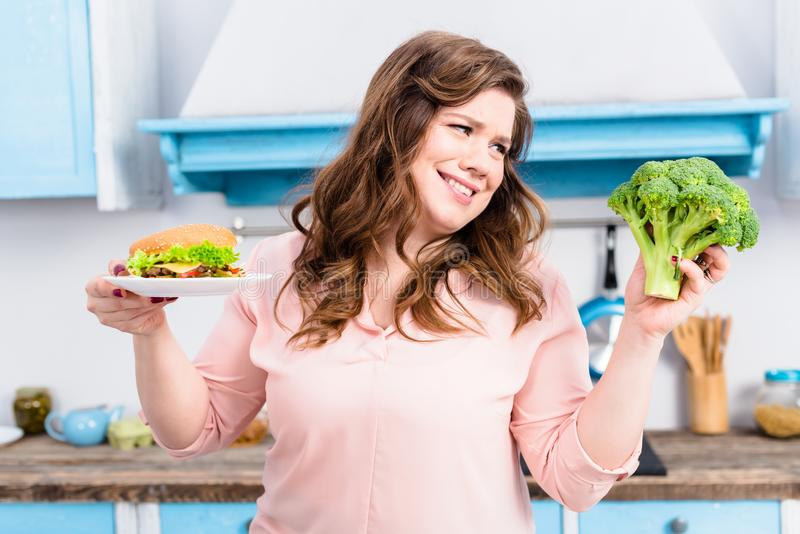 portrait of overweight woman with burger and fresh broccoli in hands in kitchen at home, healthy royalty free stock photos