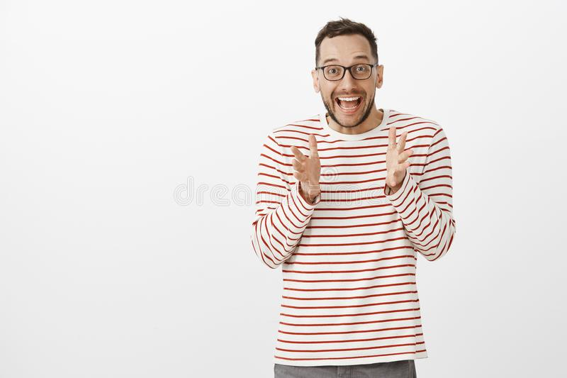 Portrait of overwhelmed cute european guy with bristle in black trendy glasses, shaking palms while explaining something. Awesome, being astonished with great stock photo