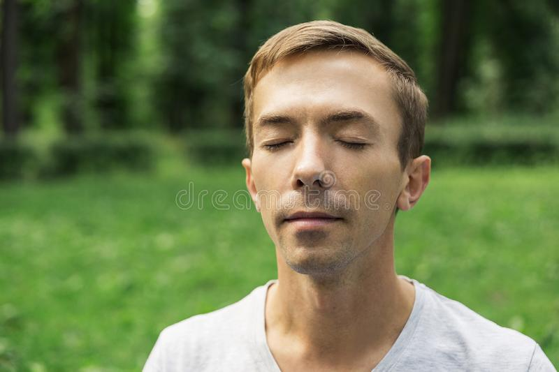 Portrait of the pacified face of a young attractive man with his eyes closed stock photo