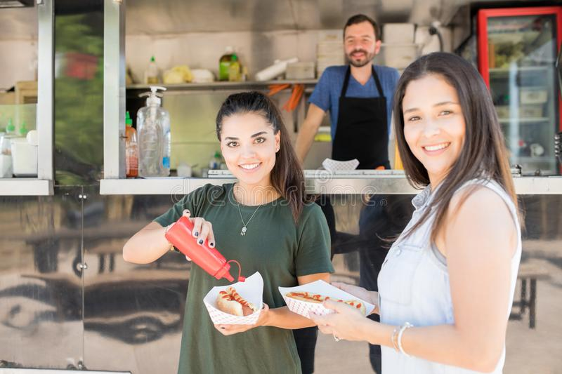 Happy girls eating at a food truck stock images