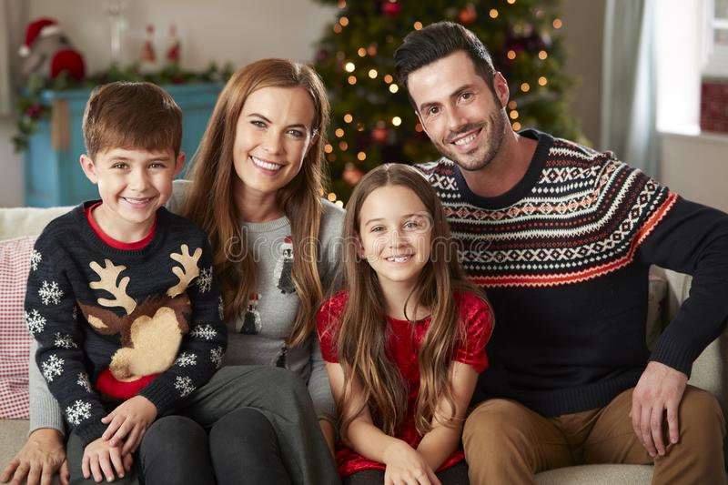 Portrait Of Parents With Children Wearing Festive Jumpers Sitting On Sofa In Lounge At Home On Christmas Day royalty free stock photo