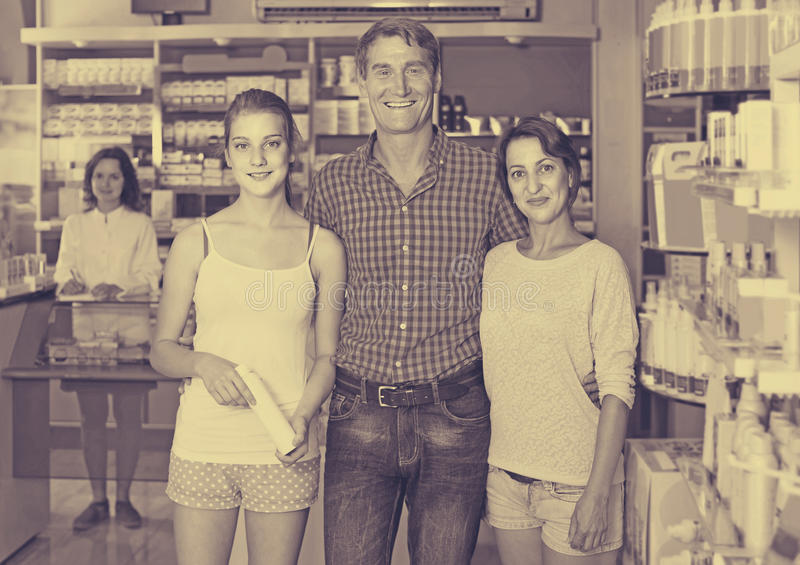 portrait of parents with daughter teenager shopping in drug stor stock photo