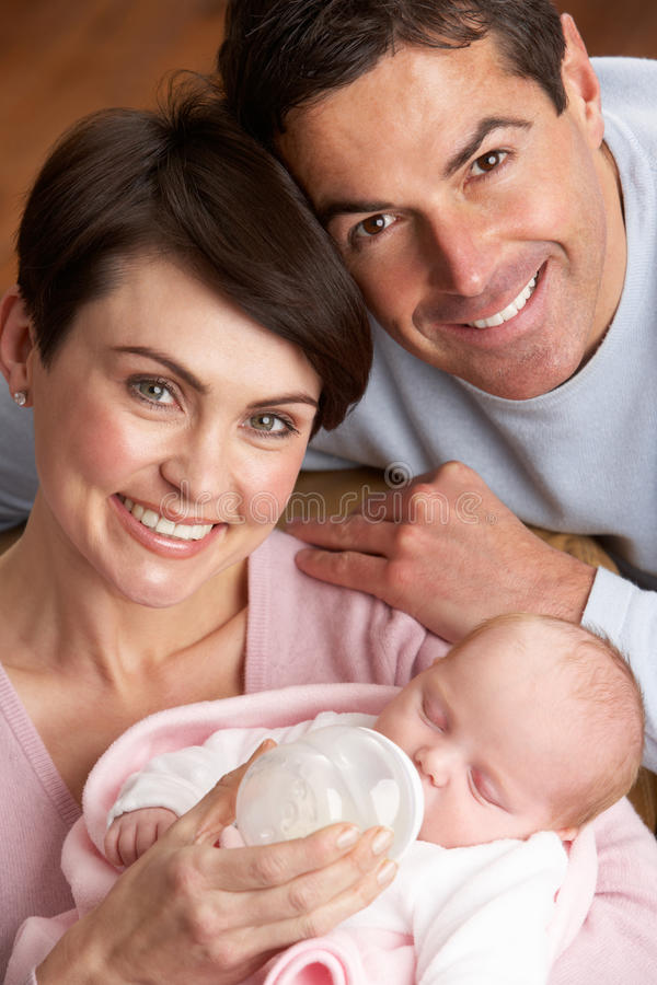 Portrait Of Parents Feeding Newborn Baby At Home royalty free stock photos