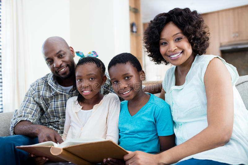Portrait of parents and their children looking at photo album in living room stock photos