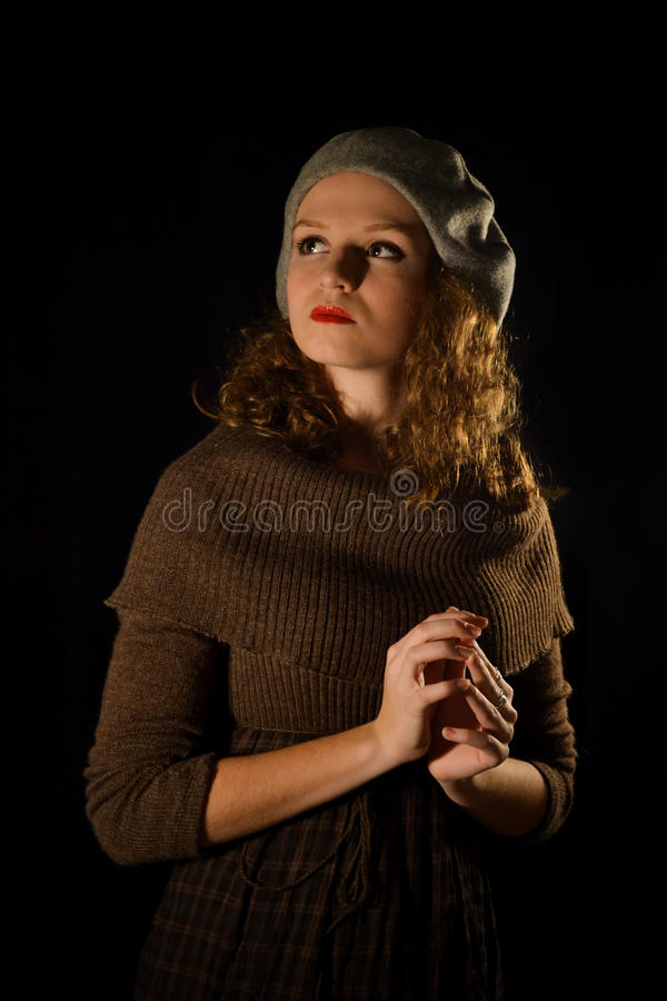 Portrait of parisian,self-assured,serious,confident,proud,high-minded girl with red lips and grey beret,brown dress.Vintage style stock photo