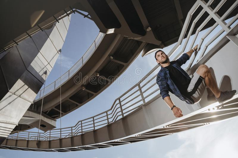 Portrait of parkour athlete climbing on the bridge. Freerunning in the city stock photos