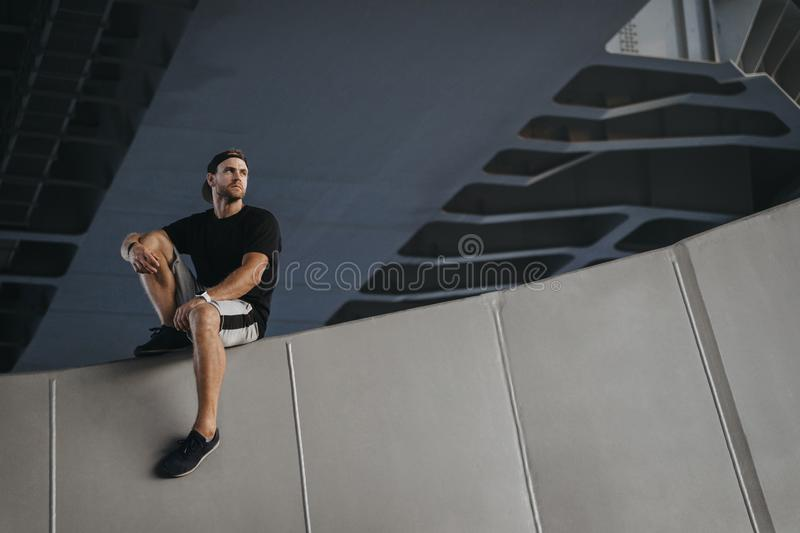 Portrait of parkour athlete sitting on edge. Of the wall after hard freerunning royalty free stock image