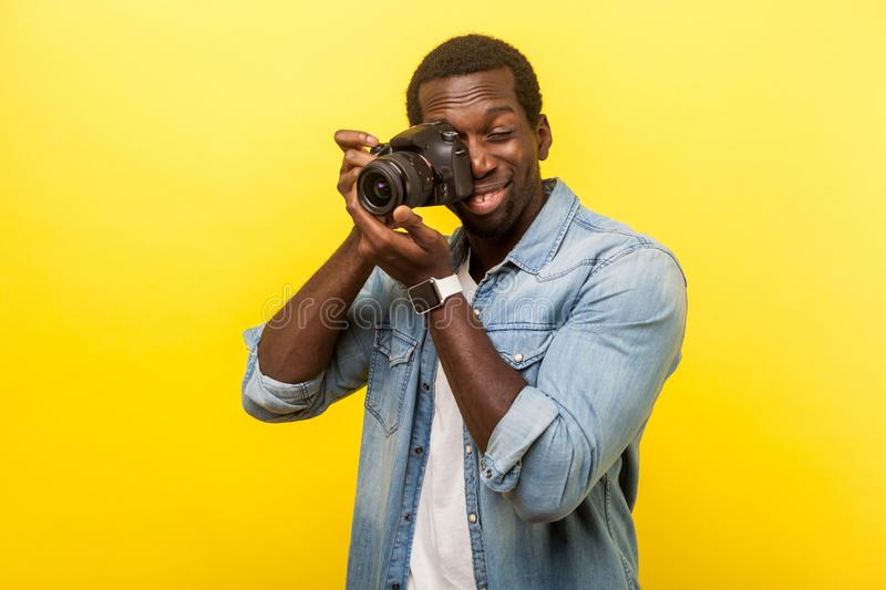 Portrait of passionate professional photographer holding digital dslr camera and focusing. indoor studio shot isolated on yellow. Portrait of passionate stock photos