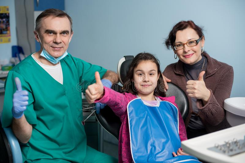 Portrait of pediatric dentist and young girl with her mother on the first dental visit at the dental office stock image