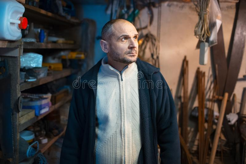Portrait of pensive adult man in his workshop room stock images