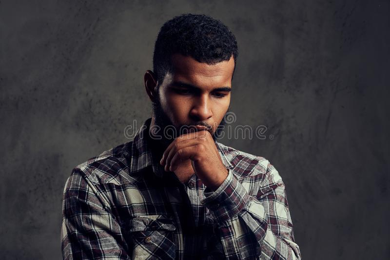 Portrait of a pensive African-American guy with a beard wearing a checkered shirt. On a dark textured background stock image