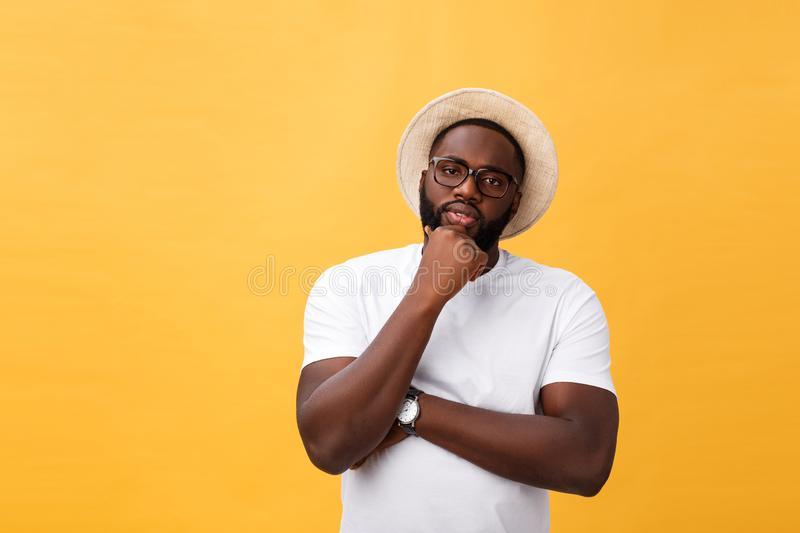 Portrait of a pensive afro american man in glasses looking up at copyspace isolated on a yellow background stock photo