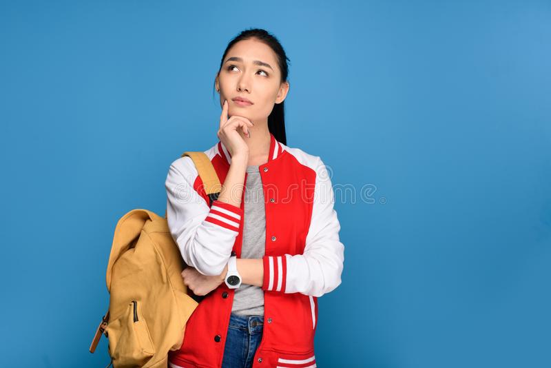 portrait of pensive asian student with backpack stock photography