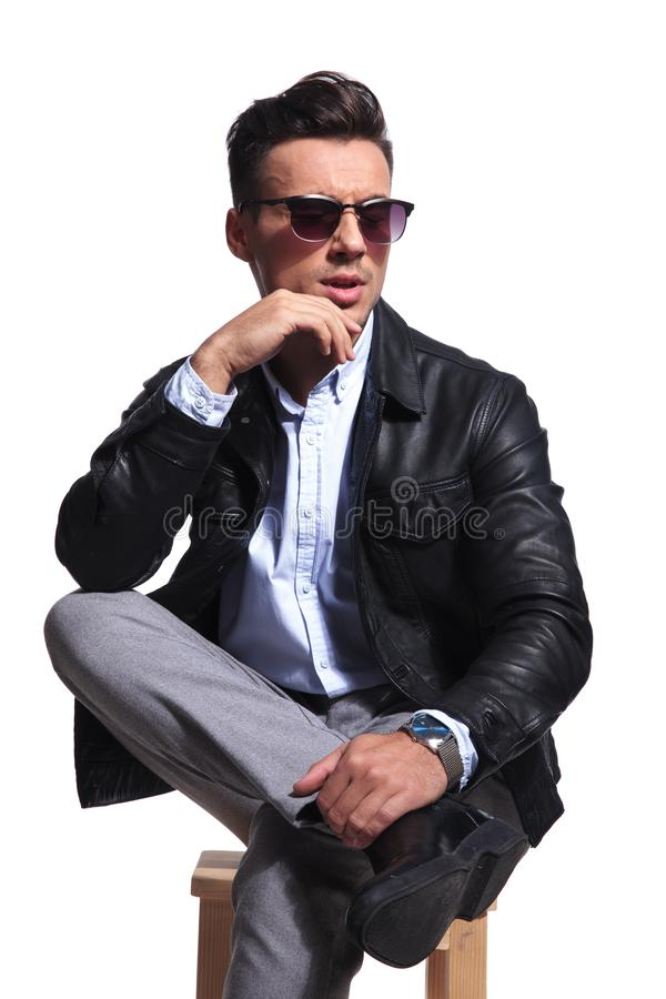 Portrait of pensive businessman with parted lips looking to side. Portrait of pensive businessman in leather jacket looking down to side while sitting on white stock image