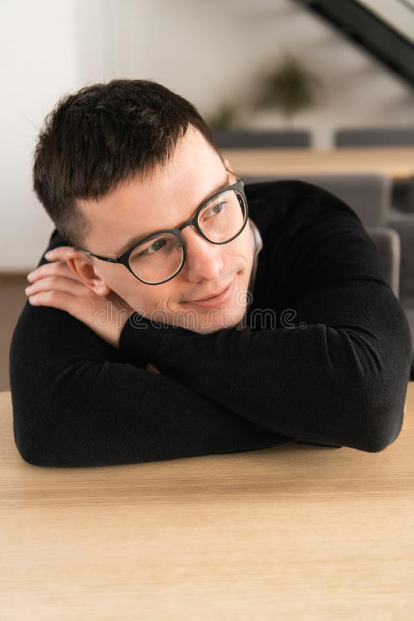 Portrait of pensive dreamy hipster guy imagines something in his mind, looks aside, being deep in thoughts. Attractive royalty free stock image