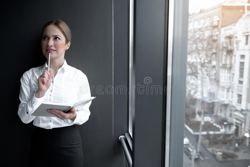 Thoughtful girl holding appointment book in hand stock photography