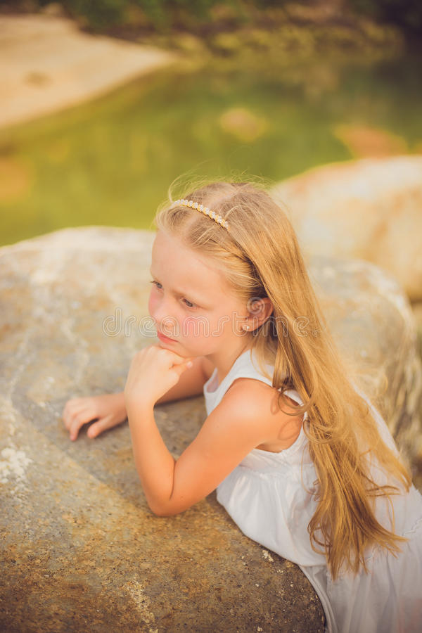 Portrait of a pensive girl in a white dress with long hair with a rim on the beach a summer day stock images