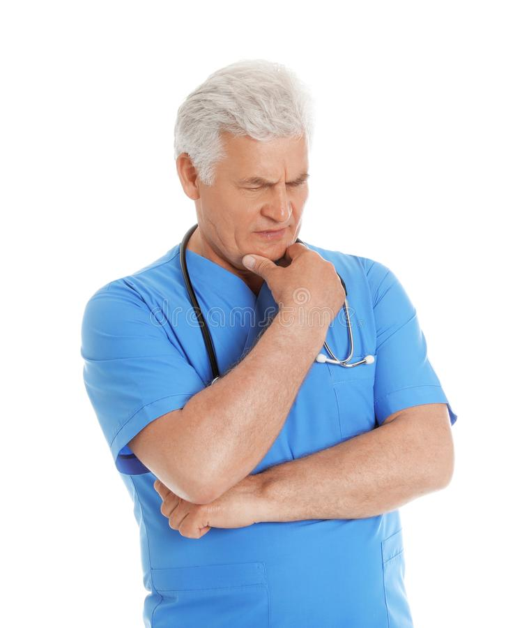 Portrait of pensive male doctor in scrubs with stethoscope isolated on white. Medical staff royalty free stock images