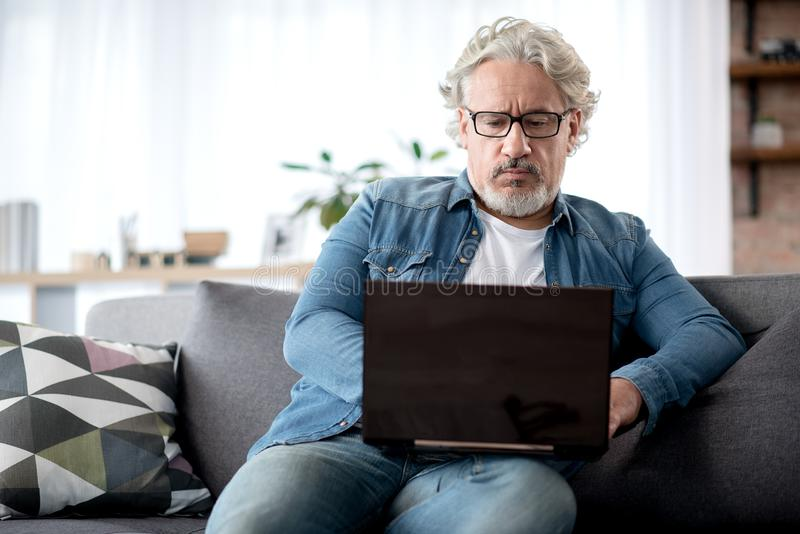 Serious elderly male typing on notebook computer stock photos