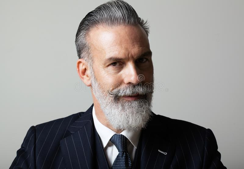 Portrait of pensive middle aged bearded gentleman wearing trendy suit over empty gray background. Studio shot, business stock photography