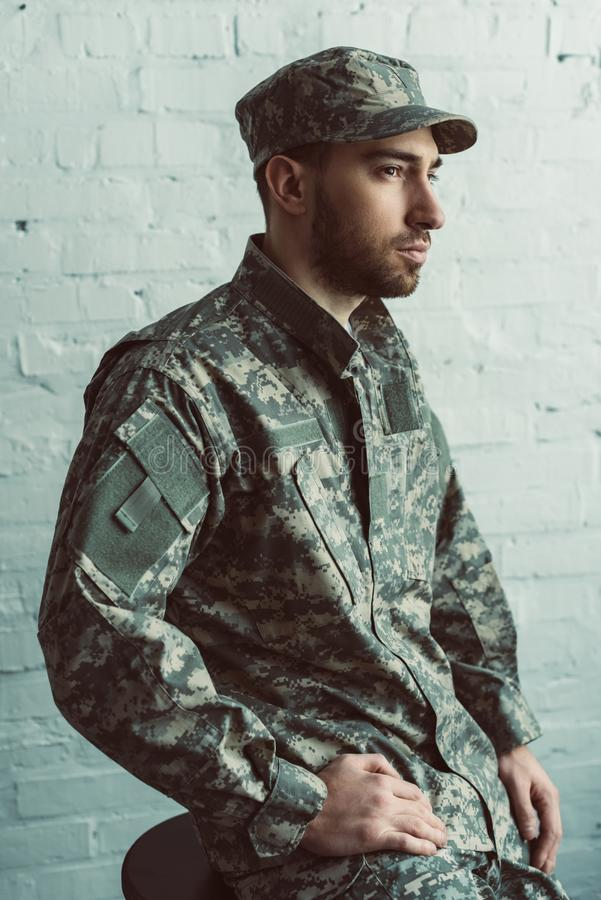 Portrait of pensive soldier in military uniform sitting on chair against white. Brick wall stock photo