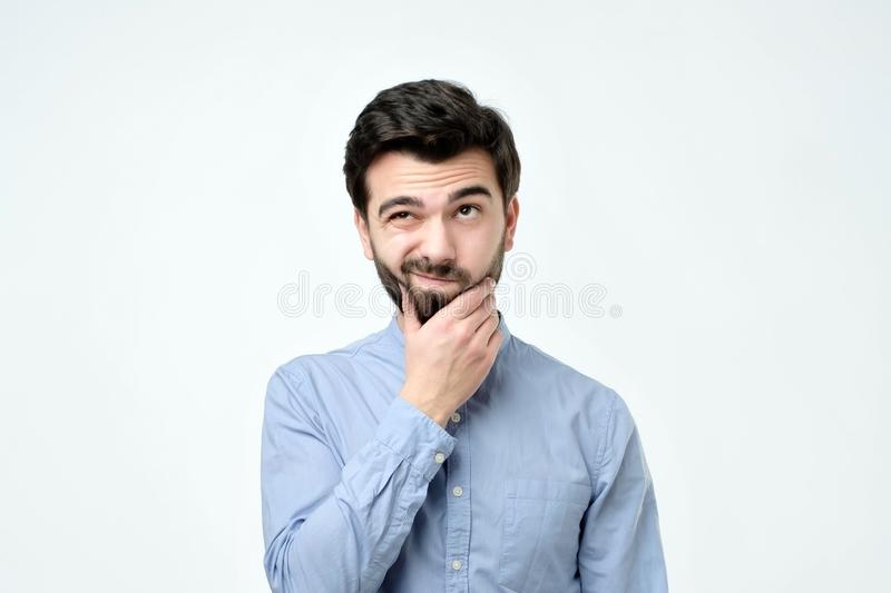 Pensive spanish man in blue shirt against a white background stock images