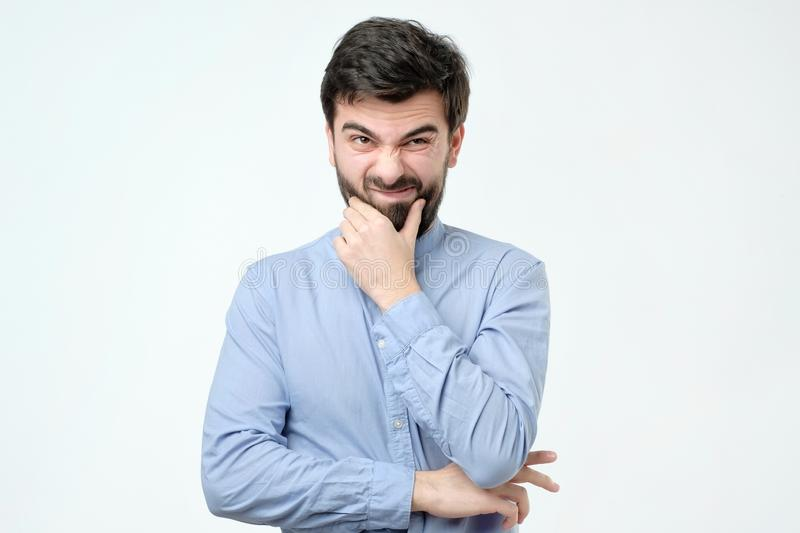 Pensive spanish man in blue shirt against a white background royalty free stock image