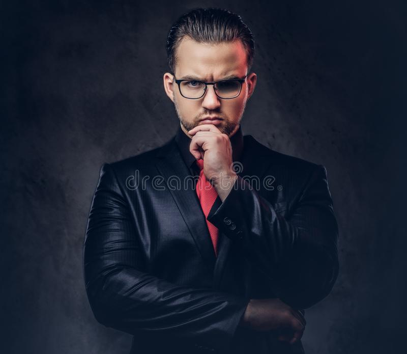 Portrait of a pensive stylish male in a black suit and red tie. stock photo
