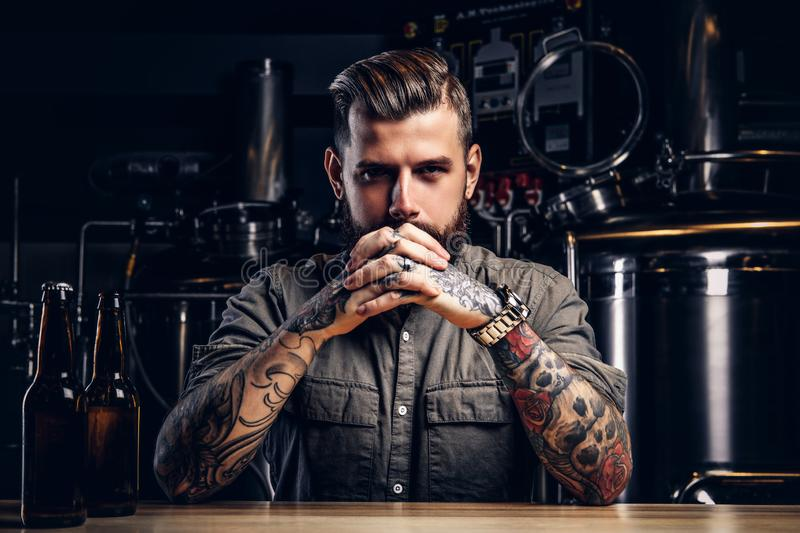 Portrait of a pensive tattooed hipster male with stylish beard and hair in the shirt in indie brewery. stock photo