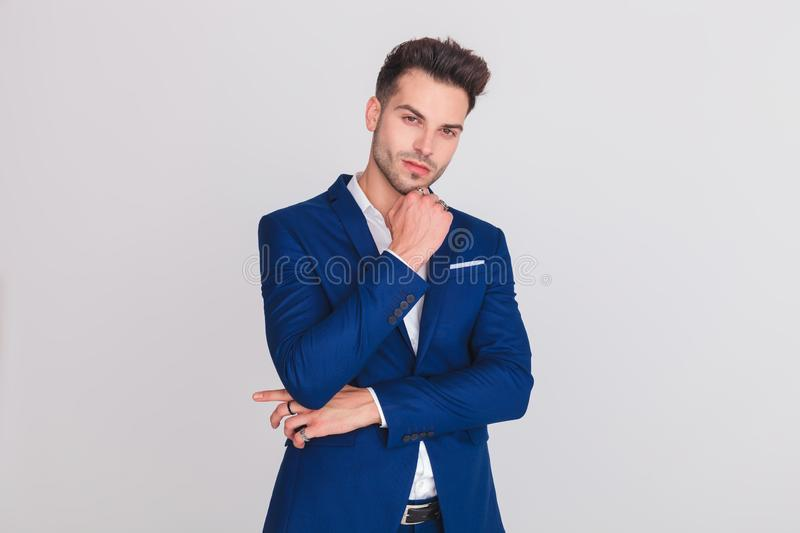 Portrait of pensive young man wearing a blue suit. Standing on light grey background stock photo