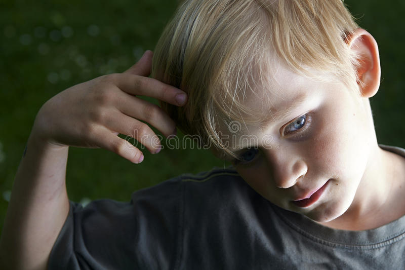 Portrait of pensive youngster (child blond boy) concentrated on something royalty free stock image