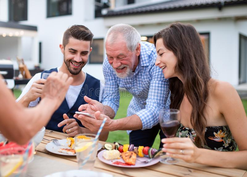 Portrait of people outdoors on family garden barbecue, taking selfie. royalty free stock images