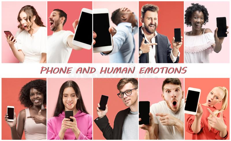 Portrait of people showing screen of mobile phone isolated over coral background stock image