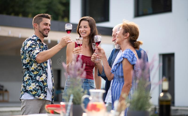 Portrait of people with wine outdoors on family garden barbecue. stock photo