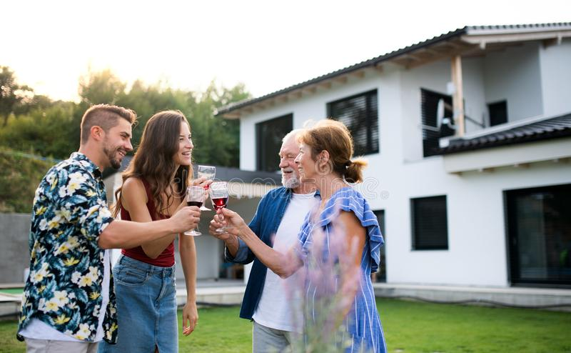 Portrait of people with wine outdoors on family garden barbecue. stock image