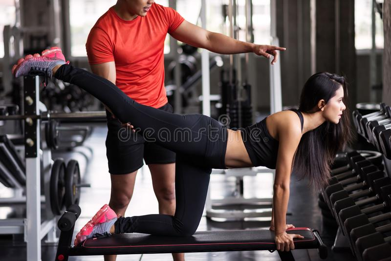 Trainer coach stretching leg to girl in gym. Portrait of personal trainer help stretching leg to beauty Asian tan women in fitness sport gym. Sexy girl working stock photo