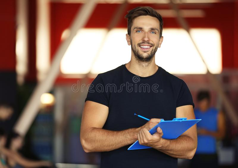 Portrait of personal trainer holding clipboard. With training plan in gym royalty free stock photo