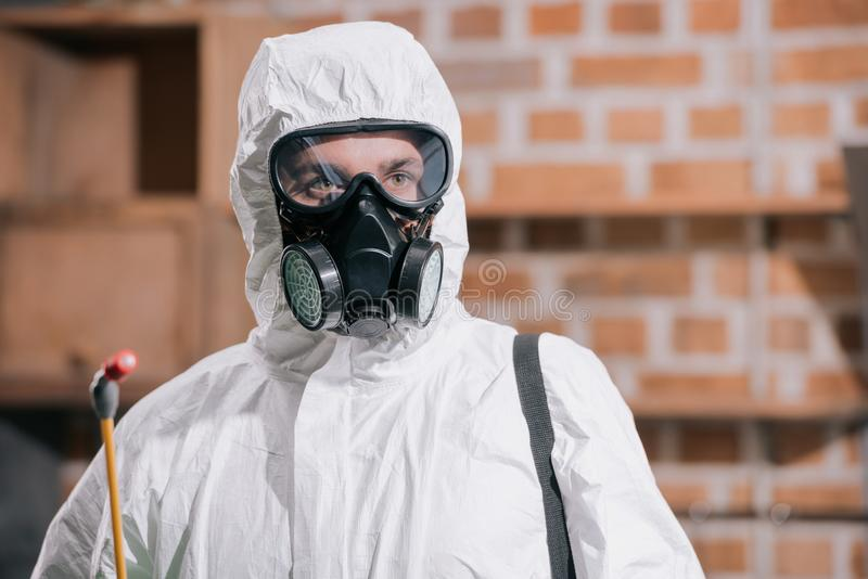 portrait of pest control worker standing in respirator and holding sprayer stock photography
