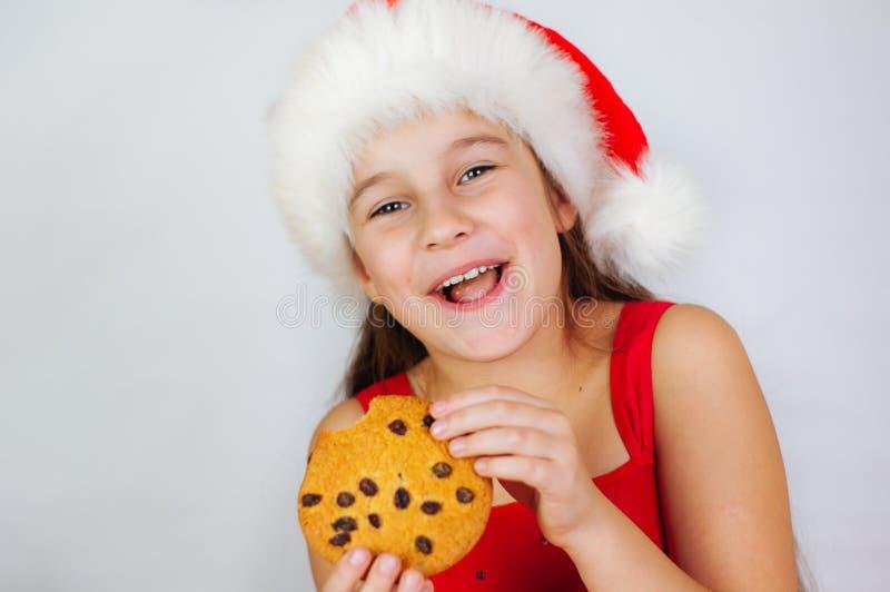 portrait petite fille mignonne à santa qui mange des biscuits de Noël photos libres de droits