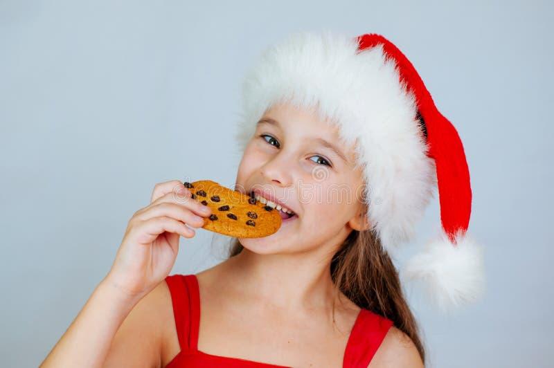 portrait petite fille mignonne à santa qui mange des biscuits de Noël photo stock