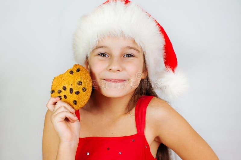 portrait petite fille mignonne à santa qui mange des biscuits de Noël image stock