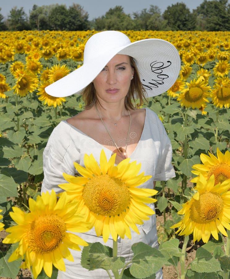 Portrait PF une jeune et belle femme regardant la caméra dans un domaine de tournesol utilisant un chapeau surdimensionné images libres de droits