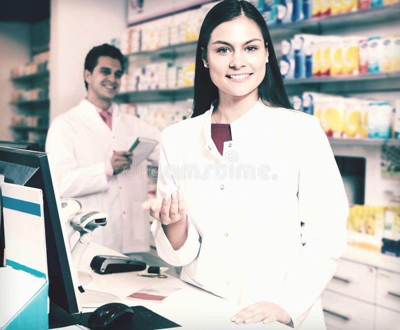 Portrait of pharmacist and assistant working royalty free stock photography