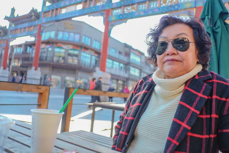 Portrait photo of Asian senior women drinking Coffe on Qianmen street The famous street in beijing. Portrait photo of Asian senior woman drinking Coffe on royalty free stock photography